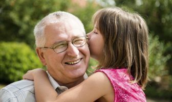 older man smiling as granddaughter whispers in ear